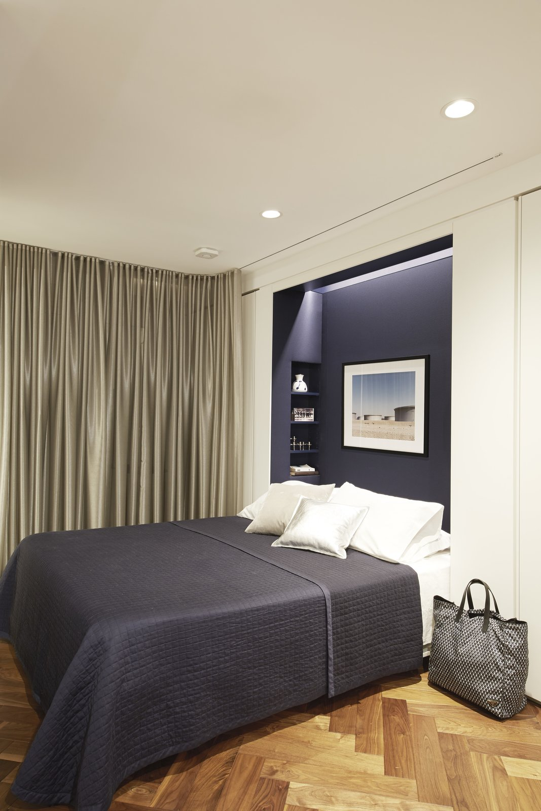 The Murphy bed niche is lined in deep blue fabric by Knoll. Tagged: Bedroom, Bed, Medium Hardwood Floor, and Recessed Lighting.  Photo 9 of 11 in In Just 450 Square Feet, A New York Architect Crafts a Multifunctional Apartment of His Own