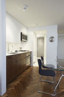 Cozy and Compact: 10 Tiny Homes in the Big Apple - Photo 6 of 10 - The new galley kitchen features a slim Corian countertop and backsplash over a deep walnut cabinetry. In the pantry and bathroom areas beyond, white terrazzo flooring replaces wood. The wall at the back of the shower is clad in large format Blue de Savoie stone tiles.