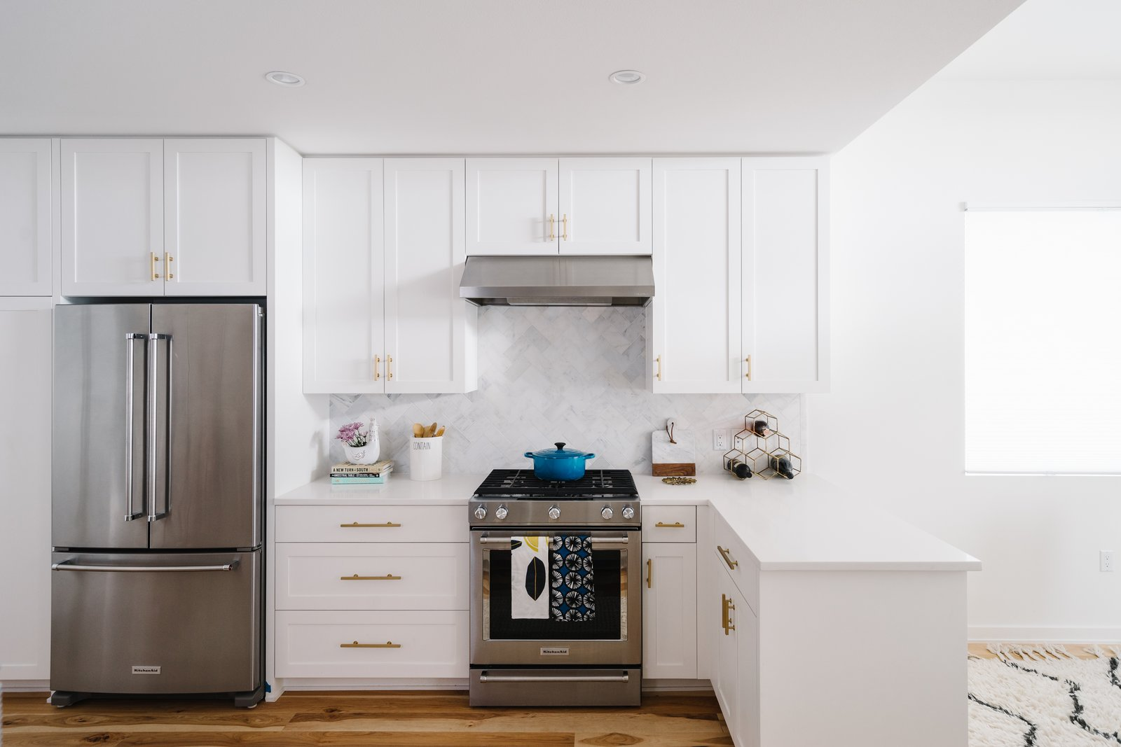 Sustainability is the Centerpiece of This New Austin Development - Photo 6 of 6 - The bright white kitchen is accented with metallic door pulls and a marble tile backsplash.