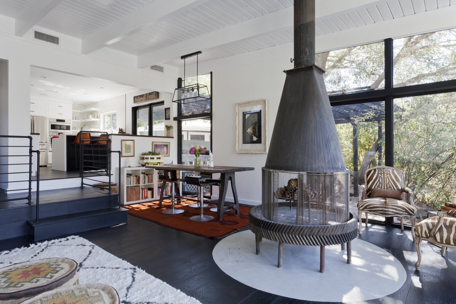 One of the home's most dramatic elements is a fireplace built from a gear from an old oil rig. To keep up with code regulations, the Hogans added a concrete base, which they customized with text celebrating the year they moved in. Tagged: Living Room, Wood Burning Fireplace, and Chair.  Photo 5 of 11 in Graphic Design Inspired This Handcrafted Canyon Hideaway