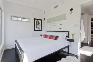 Graphic Design Inspired This Handcrafted Canyon Hideaway - Photo 6 of 10 - The couple's minimalist bedroom was imagined like a suite in a boutique hotel. There is a bedroom, closet, and bathroom, but minimal furniture as to avoid cluttering the bright white space.