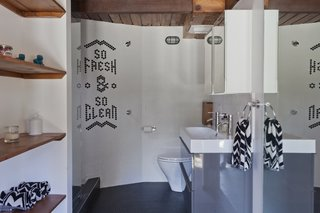 "Graphic Design Inspired This Handcrafted Canyon Hideaway - Photo 9 of 10 - Chad looked to his experience in graphic design when creating his family's home. Elements of text and graphics can be found throughout, including the inlaid tiles that spell out ""So Fresh & So Clean"" in the guesthouse bathroom."
