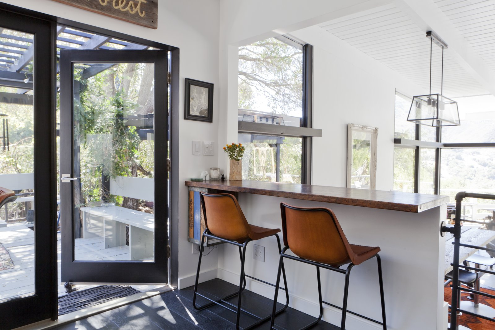 The updated kitchen and dining area is linked to the deck, which the family uses as an outdoor living space.  Photo 6 of 11 in Graphic Design Inspired This Handcrafted Canyon Hideaway