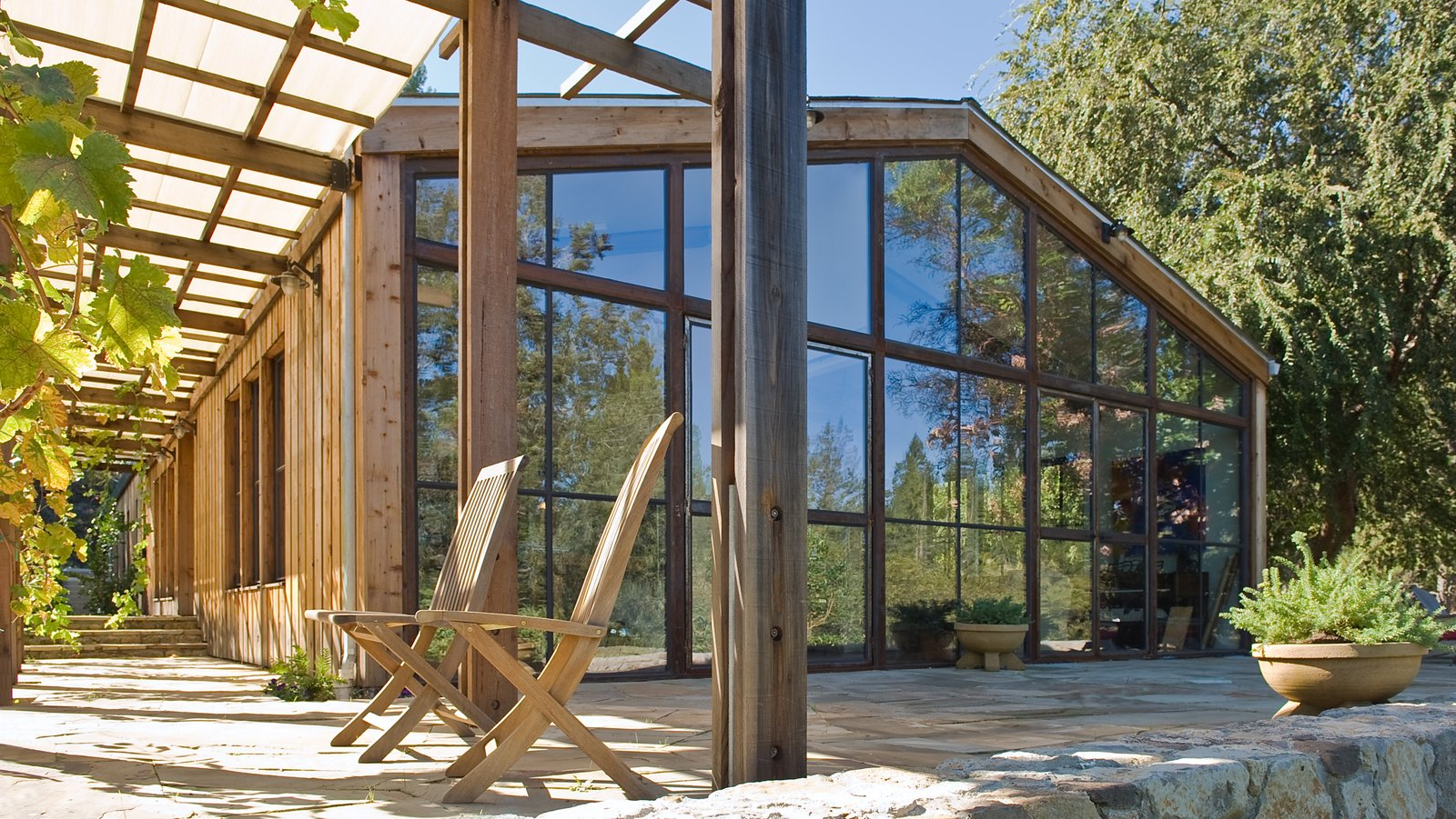 The gut renovation by Lundberg Design features cathedral ceilings, a completely glazed-end façade, and a dropped floor level in the living area. Additional elements include a Finnish soapstone stove in the center for heat; steel trusses and windows to add some visual detail; and a trellis on the front to add depth and texture to the façade. Tagged: Outdoor, Large Patio, Porch, Deck, Stone Patio, Porch, Deck, and Trees.  McDonald Residence by Lundberg Design