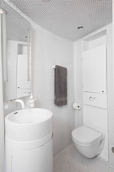Inside a converted grain silo, a bathroom is wrapped in white penny tile.  #penny #tile #bathroom