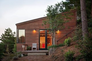The approximately 1,800-square-foot studio is clad in redwood to match the ochre terrain; its angled roof defers to the hill's incline. The windows are from Blomberg Window Systems.