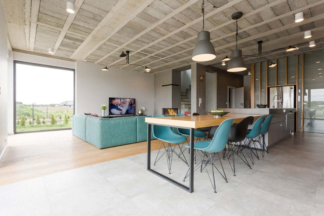 A mix of DSW and DSRA Eames Plastic Side Chairs from Vitra are seated at the dining table, which extends from a stainless steel countertop. Tagged: Dining Room, Table, Chair, Pendant Lighting, and Light Hardwood Floor. Rarely Do Family Homes  Look So Raw - Photo 2 of 4