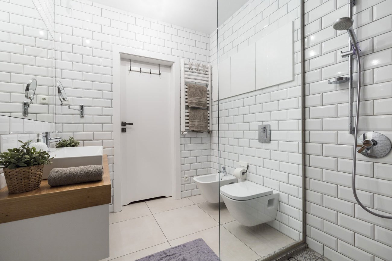 Subway tile, another fixture of the urban landscape, envelops the bathroom. Tagged: Bath Room, Ceramic Tile Floor, Vessel Sink, Full Shower, Wood Counter, Subway Tile Wall, and One Piece Toilet.  Photo 4 of 4 in Rarely Do Family Homes  Look So Raw