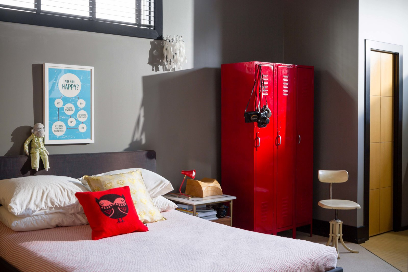 A red gym locker, repurposed as storage, is a whimsical touch in the bedroom.  127+ Inspiring Interior Ideas by Dwell from This Century-Old Bungalow Is an Eternal Work-in-Progress