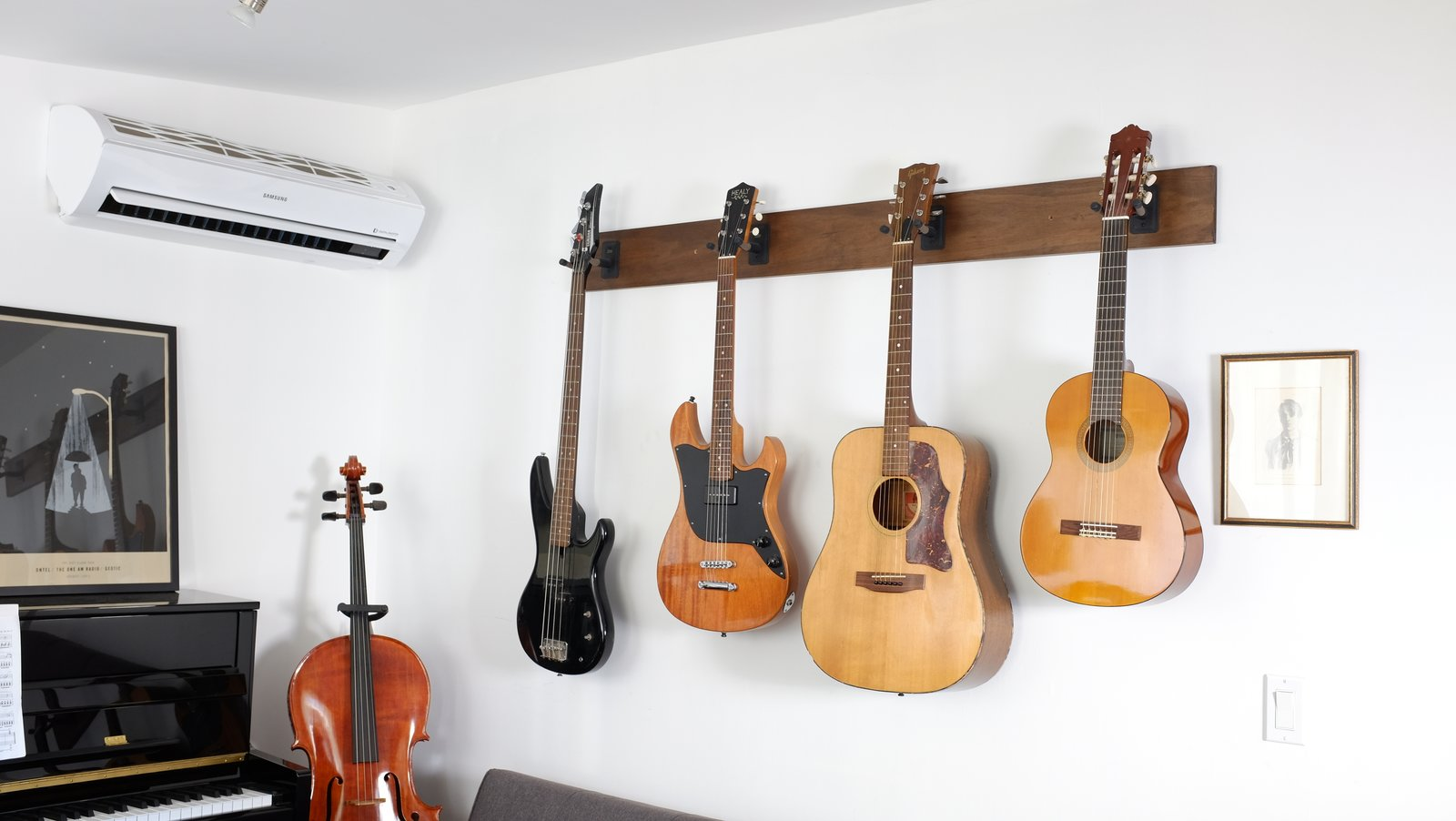 Composer and podcaster Hrishikesh Hirway hangs guitars and a bass from wall-mounts in his Echo Park home to conserve space.