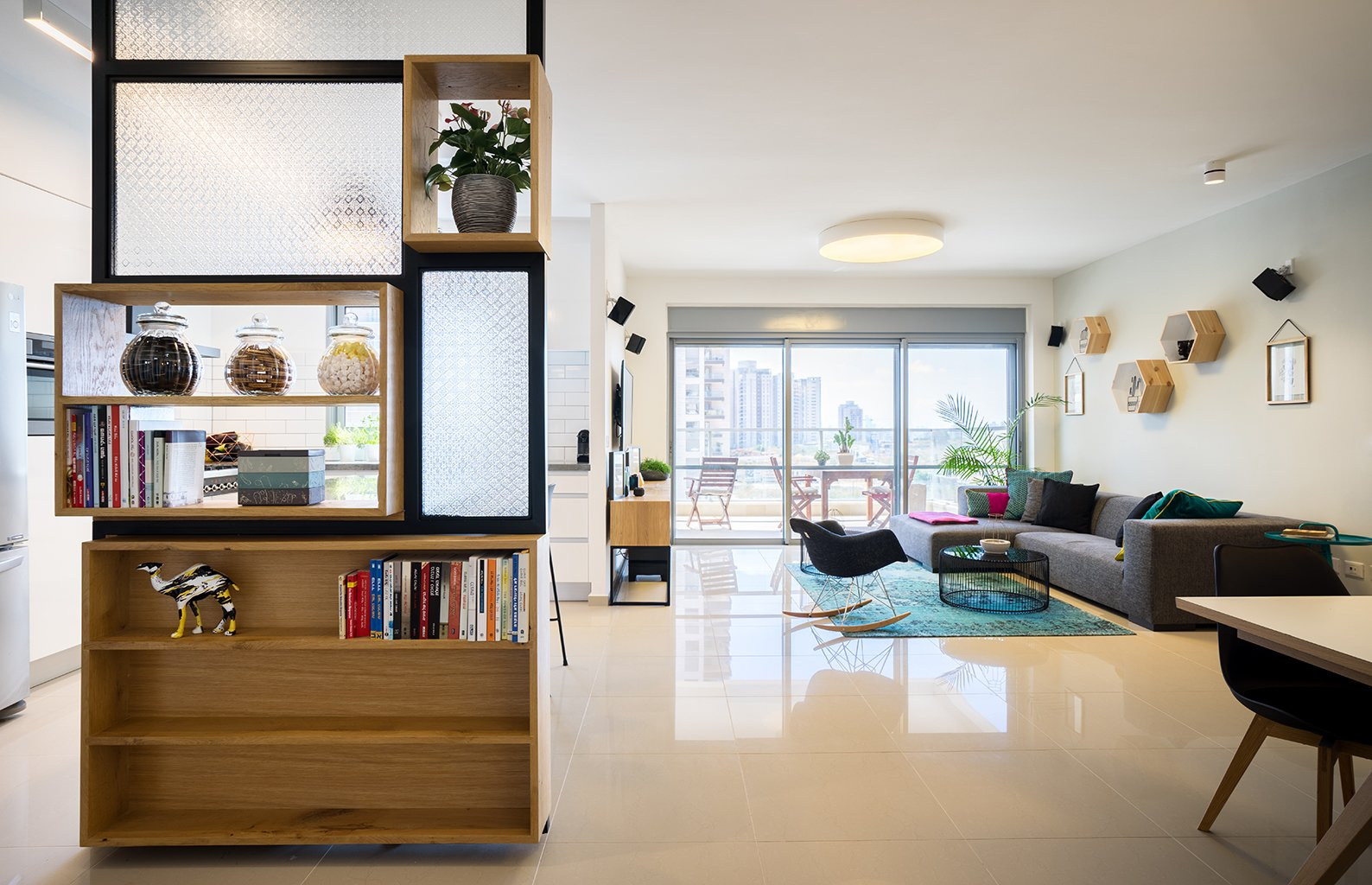 The most immediately striking feature of this 1,400-square-foot in a 21-floor high-rise is the shelving unit/room divider between the kitchen and living area. Tagged: Living Room and Sofa.  Photo 2 of 4 in A Riotous Makeover for a Generic  High-Rise Home