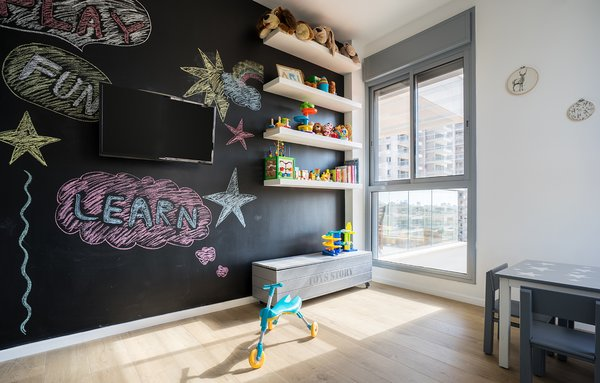 A chalkboard wall encourages creative exploration in the child's room.