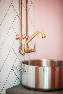 Rustic brass fixtures are attached to a wall of subway tile that has been arranged in a herringbone pattern.