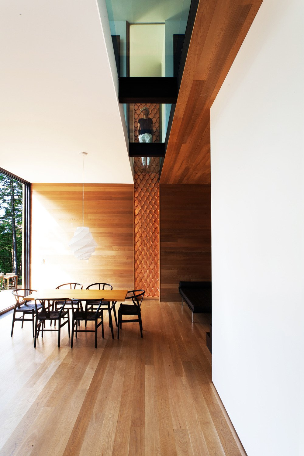 A textured wood walls meets a glass cutaway on the second floor. The Wishbone chairs are by Hans Wegner. Tagged: Dining Room, Chair, Table, Pendant Lighting, and Light Hardwood Floor.  Photo 2 of 5 in Is it Any Surprise a Sculptor Had a Hand in This Home?