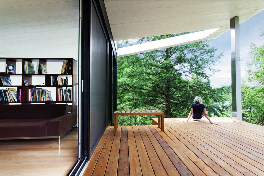 The top of the home's lower volume forms a deck. An oculus allows the residents to sun beneath the roof overhang.