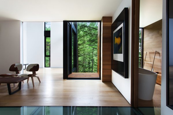 The home's lower volume frames majestic woodland views. The LCW Chairs are by Charles and Ray Eames.