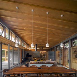 Channeling Midcentury Modern in Northern California - Photo 1 of 7 - Honest materials appear throughout this Los Altos, California, home. In the double-height living area, Mantis chairs by BassamFellows surround a custom live-edge dining table, fashioned from an old Claro walnut tree with help from Menlo Hardwoods.