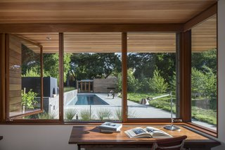 Channeling Midcentury Modern in Northern California - Photo 3 of 7 - Looking out from one of the home offices,  a board-formed concrete garden wall and linear pool draw the eye toward a guesthouse.