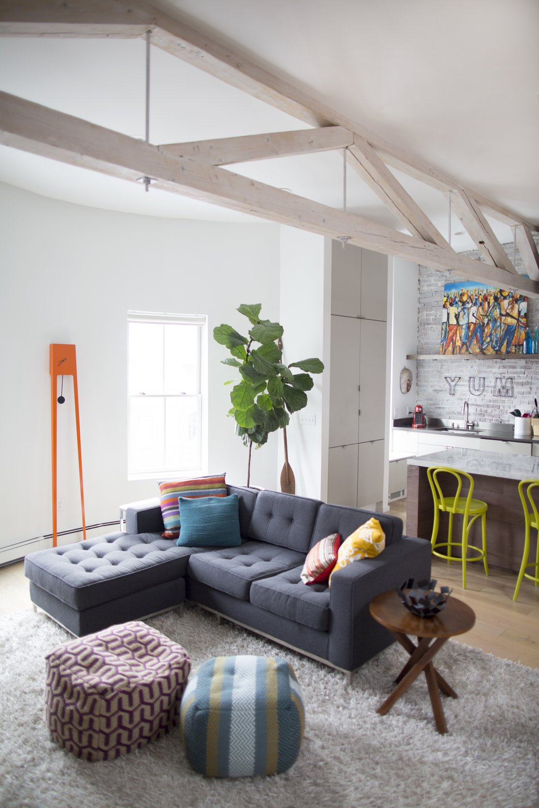 The living room features an eye-catching Tiuku grandfather clock by Covo. The Gus sofa is from Lekker. Tagged: Living Room, End Tables, Sofa, and Light Hardwood Floor.  Photo 3 of 5 in This Modern Boston Renovation Expertly Mixes in Colorful Craft Finds