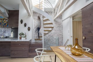 This Modern Boston Renovation Expertly Mixes in Colorful Craft Finds - Photo 1 of 4 - When Alan Ricks and Cristina de la Cierva moved into their Boston condo, a ship's ladder was taking up space in the main living area. Following a lengthy renovation, a spiral staircase provides rooftop access.