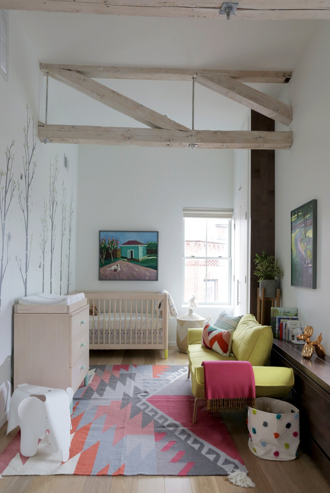 For the couple, who are expecting, adding a nursery was a key component of the renovation. The home's historic trusses were lightly sanded and whitewashed. Tagged: Kids Room, Bedroom, and Light Hardwood Floor.  Photo 5 of 5 in This Modern Boston Renovation Expertly Mixes in Colorful Craft Finds