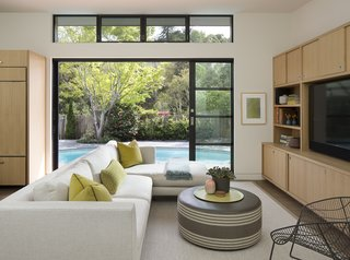Sliding glass doors connect this renovated home in Marin County to a rear terrace and kidney-shaped pool. The sectional sofa is custom by Mansfield + O'Neil Interior Design.
