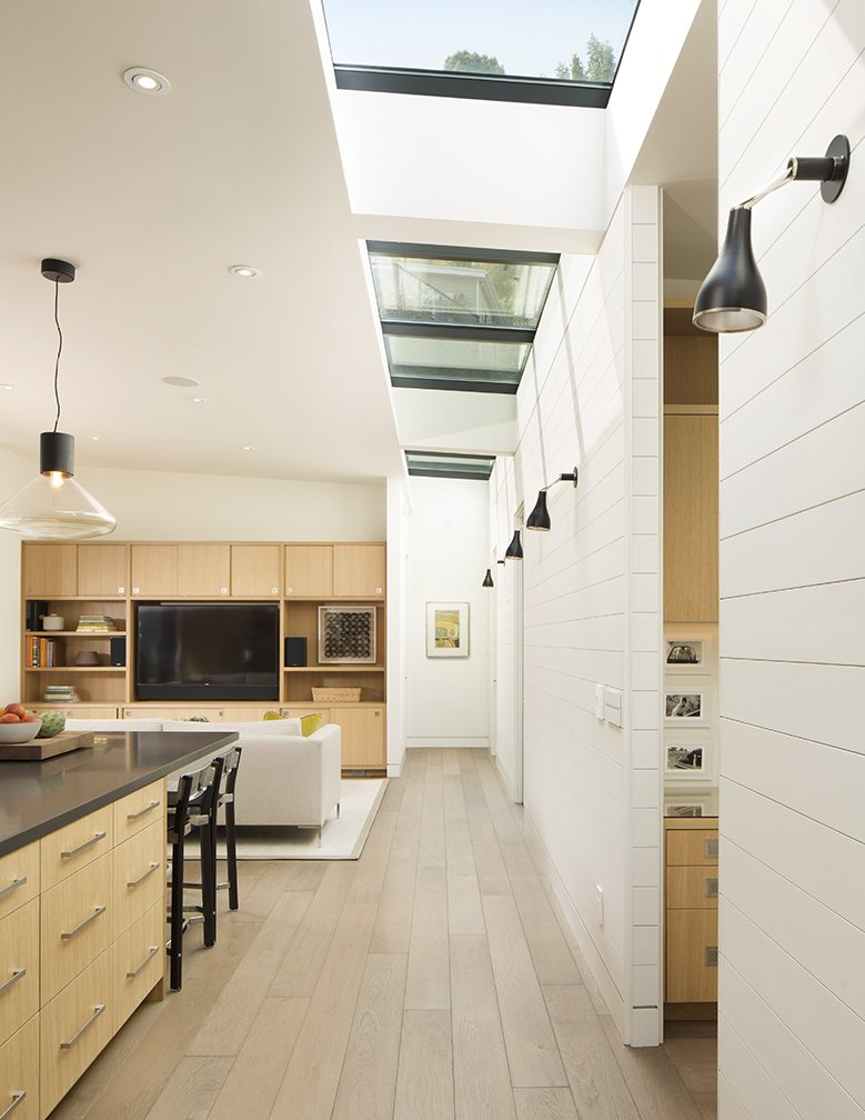 A painted wood wall marks the boundary between the home's public and private wings. Linear skylights bathe the open-plan communal area in light. A New Spin on the Suburbs in Marin - Photo 4 of 5