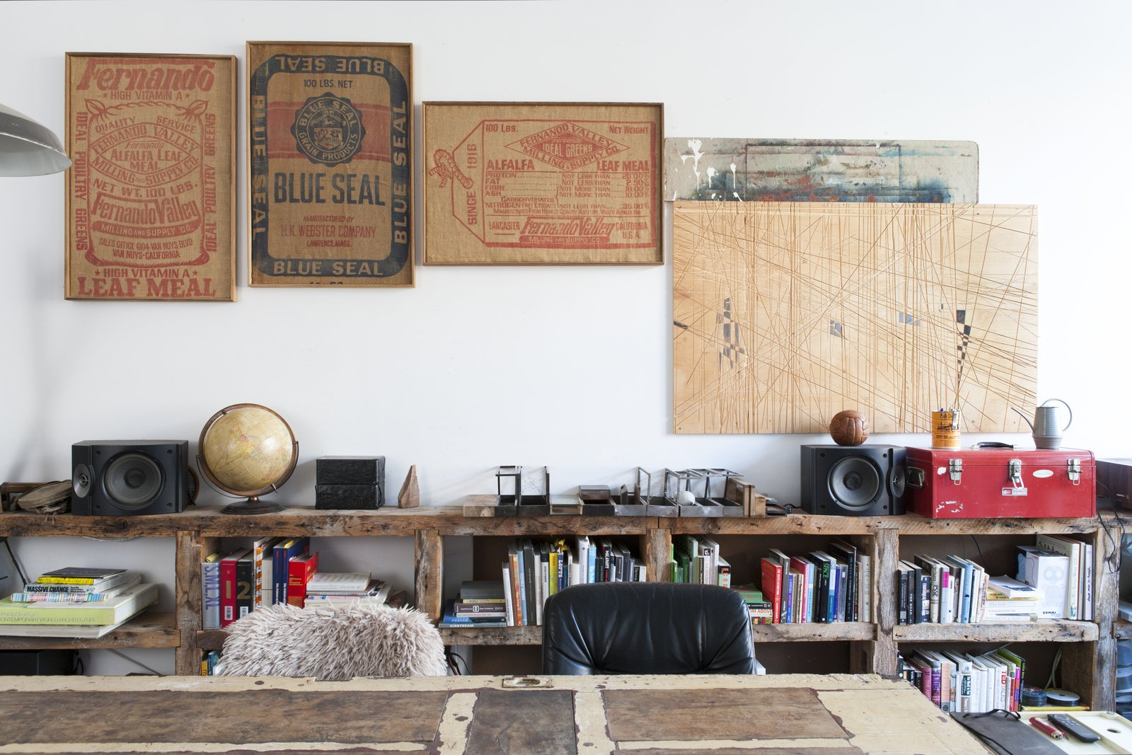 New York designer/artist Huy Bui decorated his home with a mishmash of curios, from 19th-century burlap sacks found at an antique fair to a plywood workbench he carved with a Festool plunge saw. The 17-foot-long shelving is made of old heart pine fashioned from the beams of brownstone renovation in the West Village. Tagged: Office, Desk, and Study.  Photo 2 of 5 in Huy Bui's Brooklyn Loft Is Like a Self-Contained Jungle