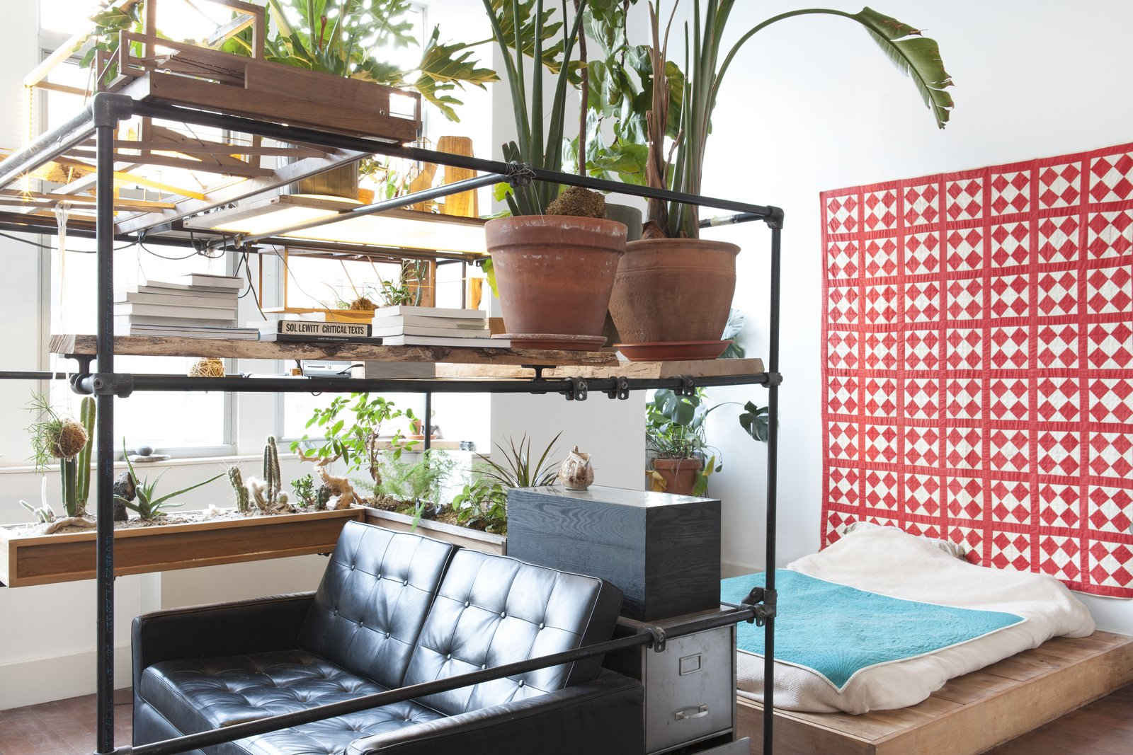 A platform bed is tucked behind a small living nook with a sofa and projector. Tagged: Shed & Studio and Storage Space.  Photo 5 of 5 in Huy Bui's Brooklyn Loft Is Like a Self-Contained Jungle