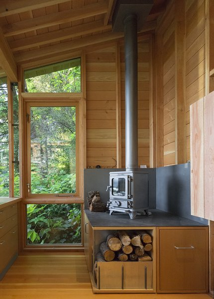 While the space is heavily insulated, with strong solar gain, a cast-iron stove from Salamander Stoves provides extra warmth on cool days. Photo 5 of Cutler Studio/Bunkhouse modern home