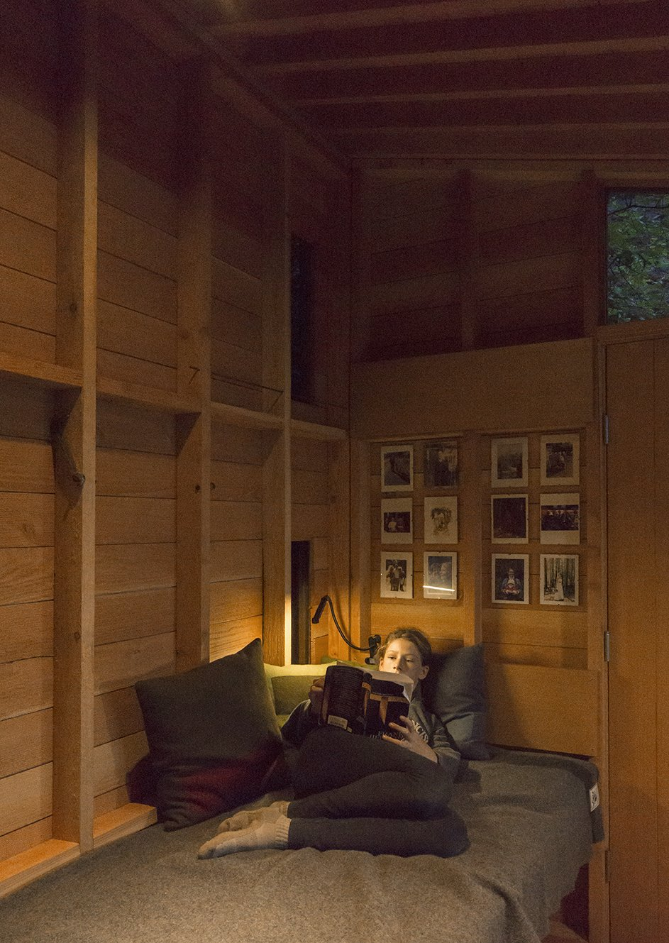 Opposite Jim's workstation, the modest interior accommodates a single bunk—Hannah's preferred reading perch.