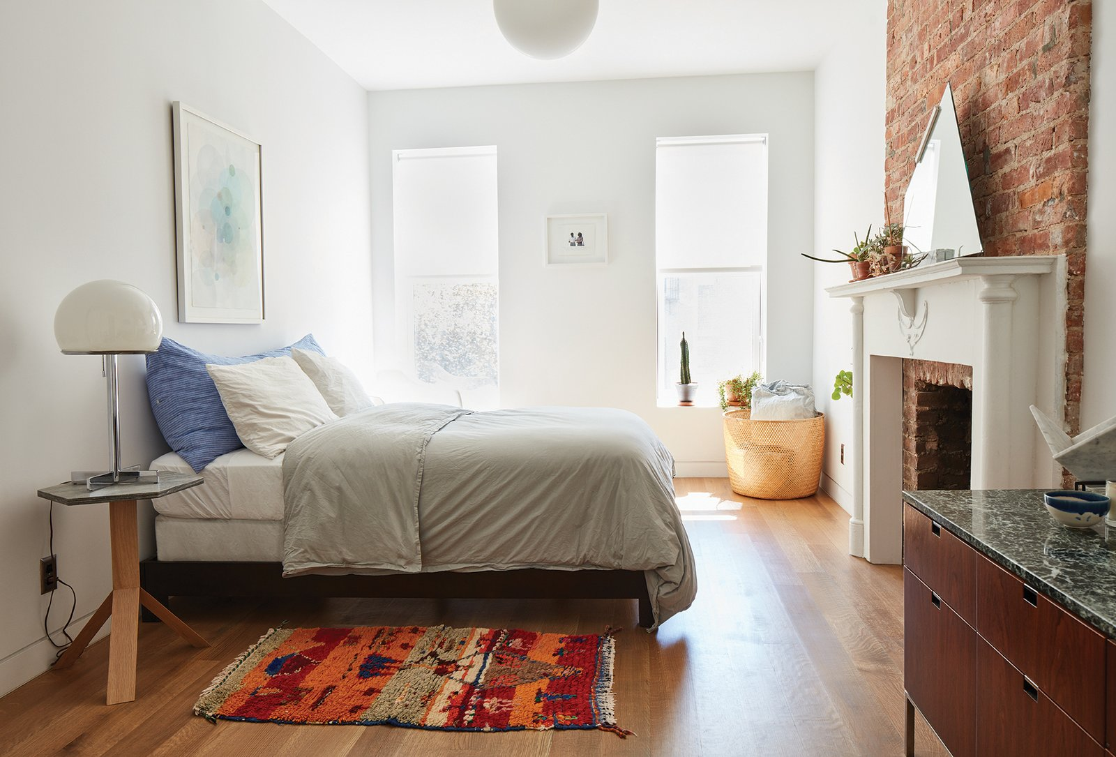 The furnishings reflect an eclectic mix of old and new. In a second-floor guest room, a bedside table by Fort Standard holds a vintage lamp. Tagged: Bedroom, Pendant Lighting, Bed, Table Lighting, and Medium Hardwood Floor.  Photo 6 of 16 in Forever Changes