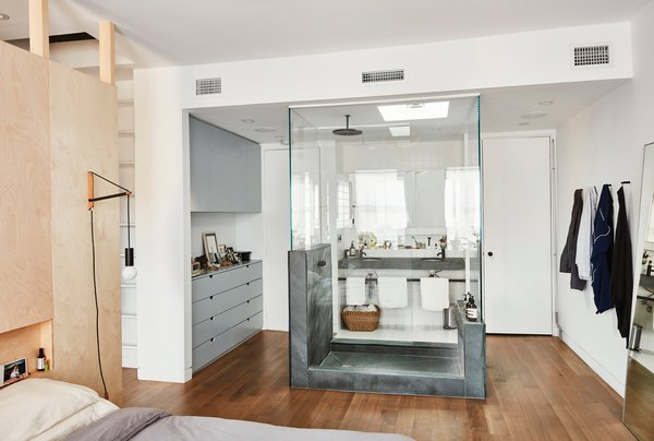 "One of the boldest moves was the glass-encased shower inside the revamped master bedroom. ""Obviously, building that shower was not a cost-saving option,"" says Keith, ""but we used green slate, which is not super expensive, either."" The Architec sinks are from Duravit."