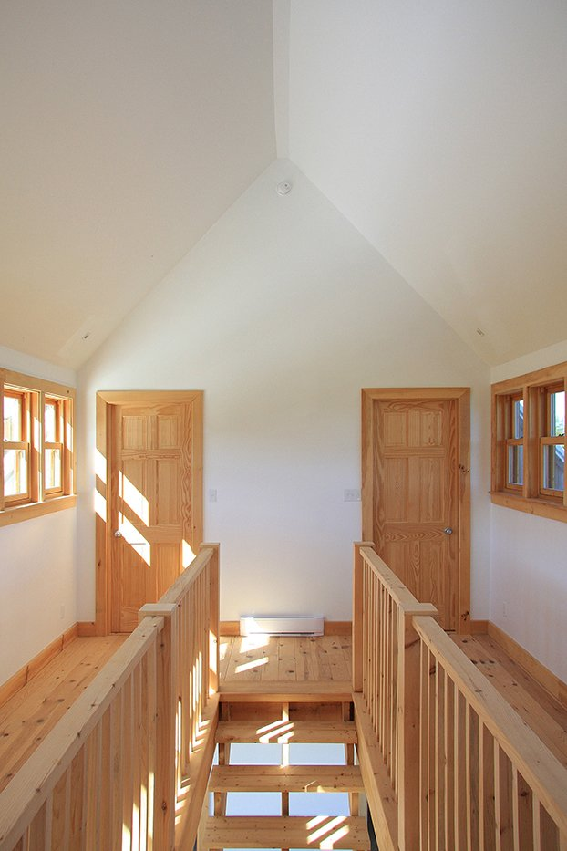 Several types of wood were used to build the house, including red pine for the floors, white cedar for the porch, and black spruce for the siding. Tagged: Hallway and Medium Hardwood Floor.  House R by Luke Hopping from Barn Raising