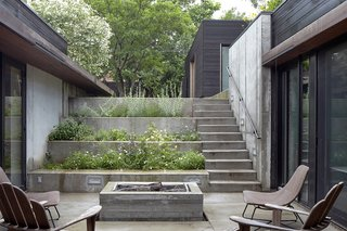 A stepped concrete garden planted with herbs and flowers marks the descent to the house. The courtyard is the focal point of the U-shaped structure; there is clear visibility between the kitchen on one side and the children's bedrooms on the other.