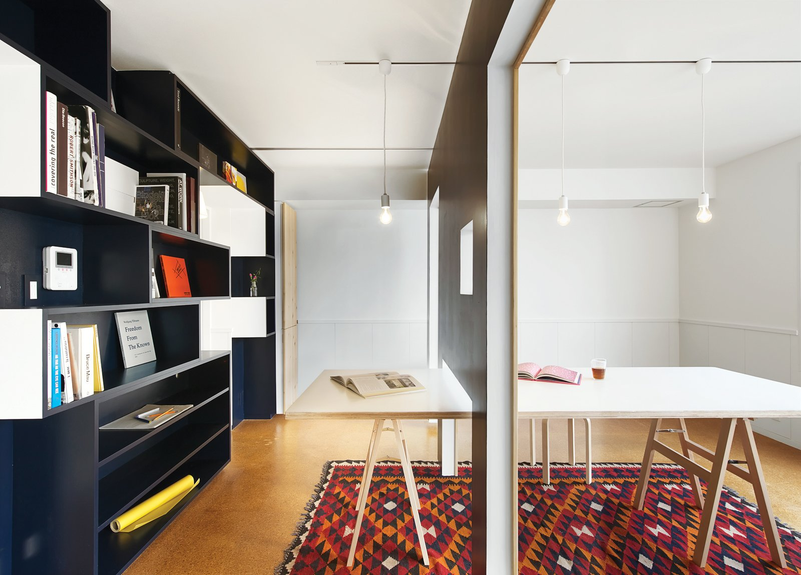 A movable wall clad in wainscoting on one side slides along tracks in the dining-room ceiling, dividing the room into a meeting space and a library. The Shiro Simple Modern Pendant lights can be easily removed and reattached after moving the wall. Tagged: Office, Study, Medium Hardwood Floor, and Desk.  30+ Modern Homes With Libraries by Matthew Keeshin