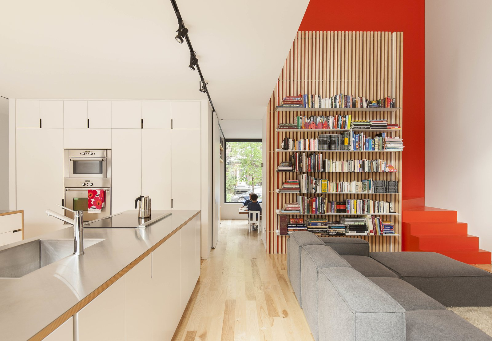 The open-plan kitchen and living room in the de Gaspé House in Montreal's Villeray neighborhood borrows natural light from a double-height space over the seating area.