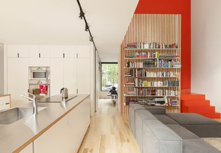 12 Functional Modern Home Libraries - Photo 9 of 12 - The open-plan kitchen and living room in the de Gaspé House in Montreal's Villeray neighborhood borrows natural light from a double-height space over the seating area, augmented by the colorful staircase framing the bookshelves.