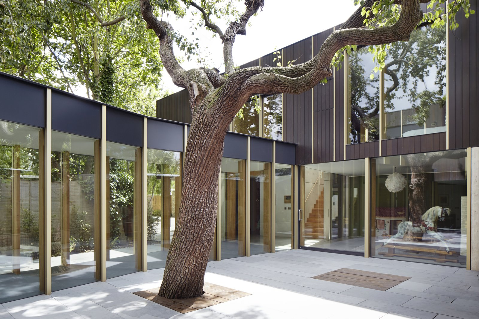 Tagged: Outdoor, Concrete Patio, Porch, Deck, Pavers Patio, Porch, Deck, and Trees.  Photo 2 of 9 in This Modern Courtyard Home Celebrates a 100-Year-Old Tree