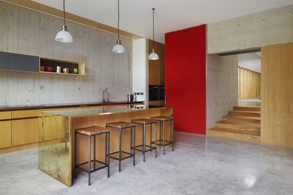 The other centenarian fixtures in the home are the glass light shades in the kitchen. The shades originally hung in an old chapel. The brass bar was designed by the firm. Tagged: Kitchen, Pendant Lighting, and Metal Counter.  Homes by Andrea D. Smith from This Modern Courtyard Home Celebrates a 100-Year-Old Tree