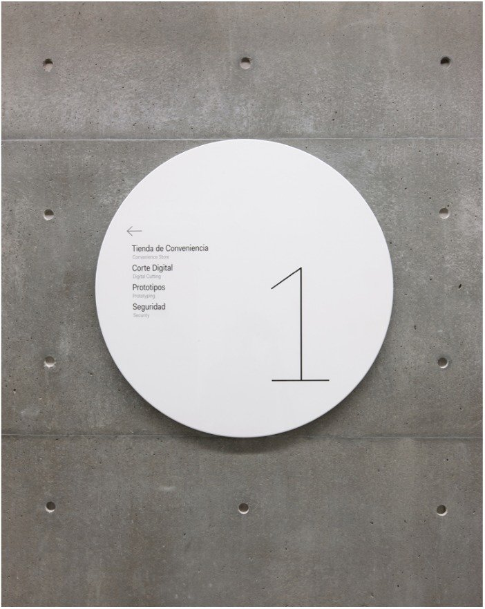 Identification and wayfinding signage appears on shiny metal discs that stand in contrast to the building's textured concrete walls.