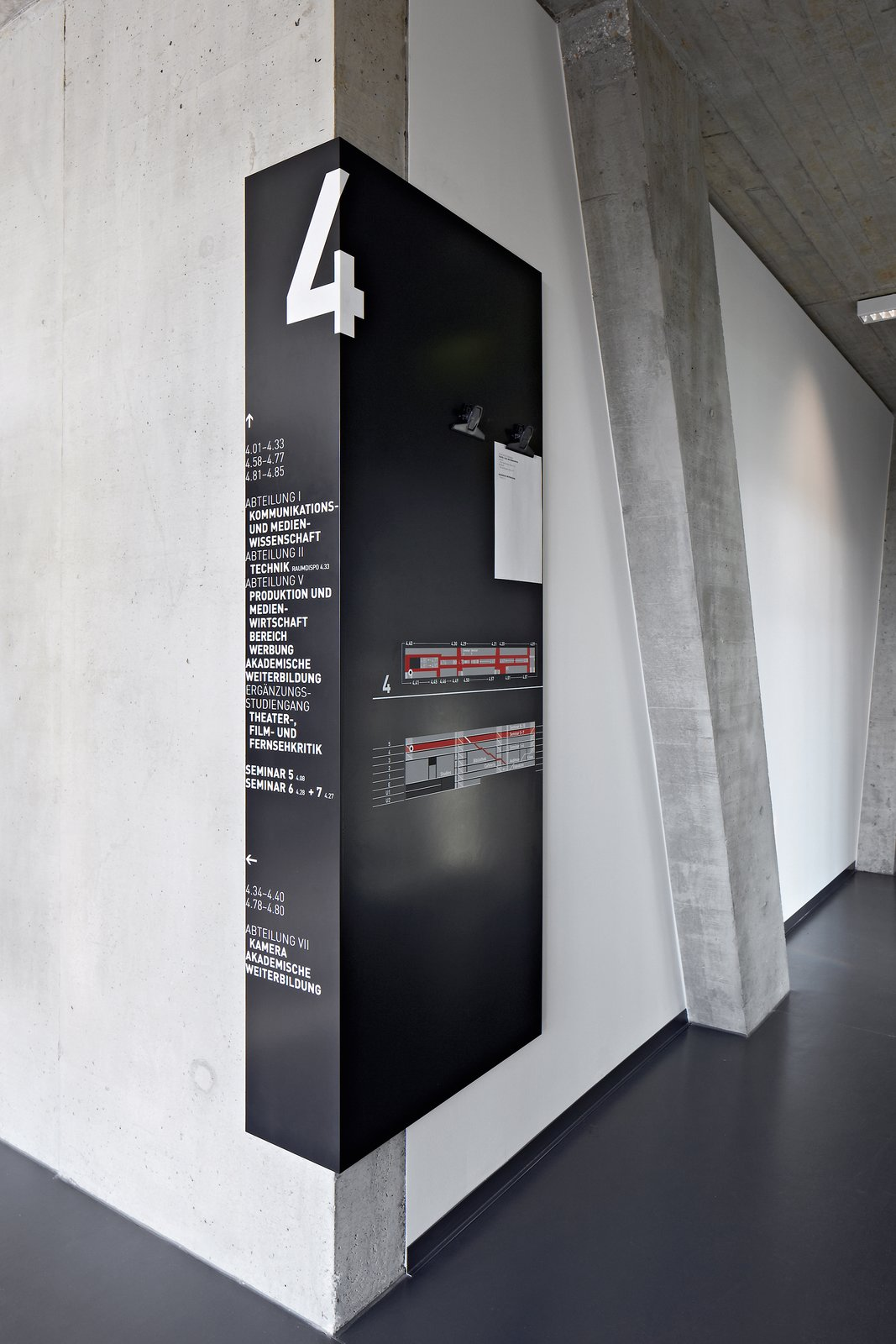 University of Television and Film Munich: More detailed information is contained on distinctively designed black signs that wrap around corners almost like shadows, so that they can be easily seen from the floors and the central staircase.  Way-Finding Systems by Rob Hewitt