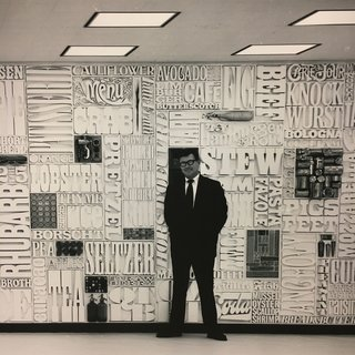 "New York's Hidden  Graphic Design Gem - Photo 4 of 6 - Lou Dorfsman standing infront of ""Gastrotypographical"". With the help of Tom Carnase, Herb Lubalin worked extensively on this typographic ""wall of words"" that spanned 35 feet in width and 8 feet in height. It was situated in the cafeteria at the CBS headquarters in New York City. The concept was to treat the wall like a giant typesetter's case, with a lock-up of words and objects on the theme of food. 1966"