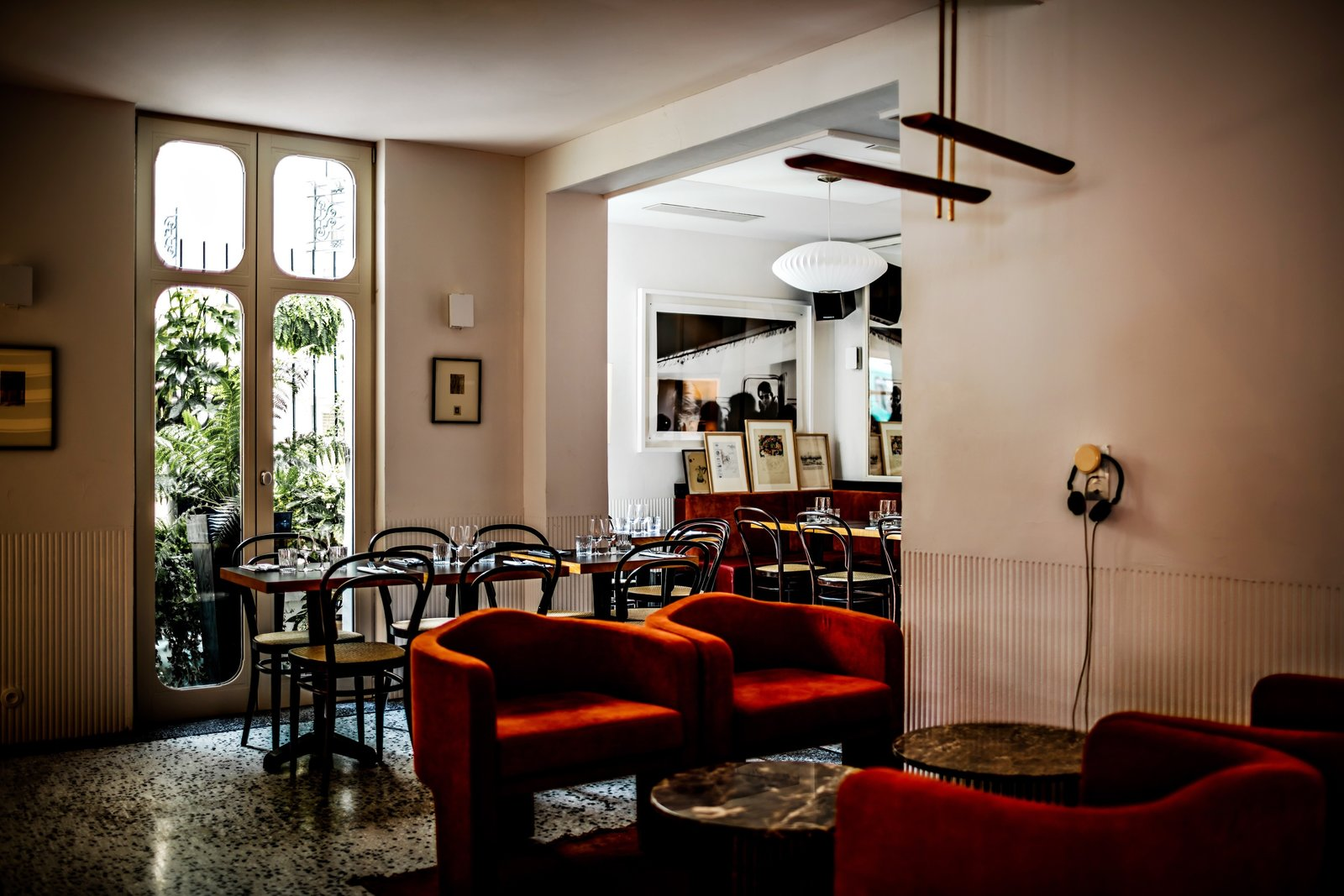 The hotel's restaurant spills into the lobby, promoting the idea that the ground floor functions more as a whole and less as individual spaces.  Photo 7 of 8 in Collaboration Reigns  Over This Parisian Neighborhood Hotel