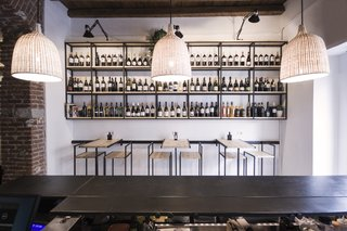Bringing a Taste of  Sicily to Milan - Photo 4 of 5 - Shown here is a frontal view of the Studio DiDeA-designed bar stools and tables that are connected to a sliding track system. Above these furnishings, modular shelves feature a selection of wines available for sale.