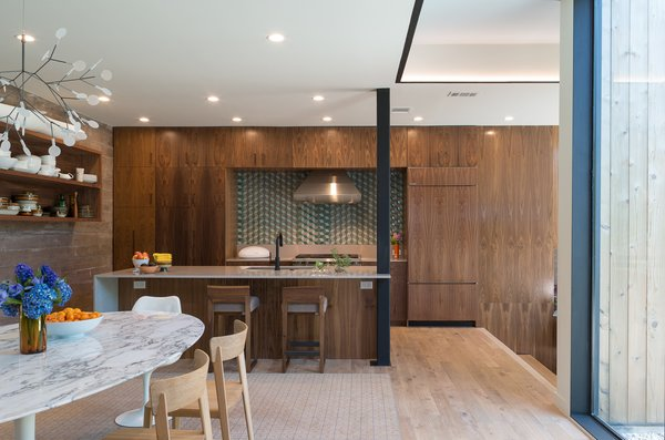 Modern home with kitchen, light hardwood floor, marble counter, ceramic tile backsplashe, and wood cabinet. Photo 6 of Tetra House