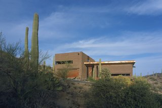 These 7 Homes in the Southwest Show How to Design For the Desert - Photo 5 of 7 - Three pavilions of masonry, rusted steel, and glass come together in Tucson, Arizona, to create a home designed by Ibarra Rosano Design Architects that draws inspiration from the desert landscape. Each facade is in direct response to the sun, wind, topography, vegetation, and views. Windows are long and shaded, entryways are covered, and views are curated to capture indirect sunlight and provide vistas of the landscape beyond.