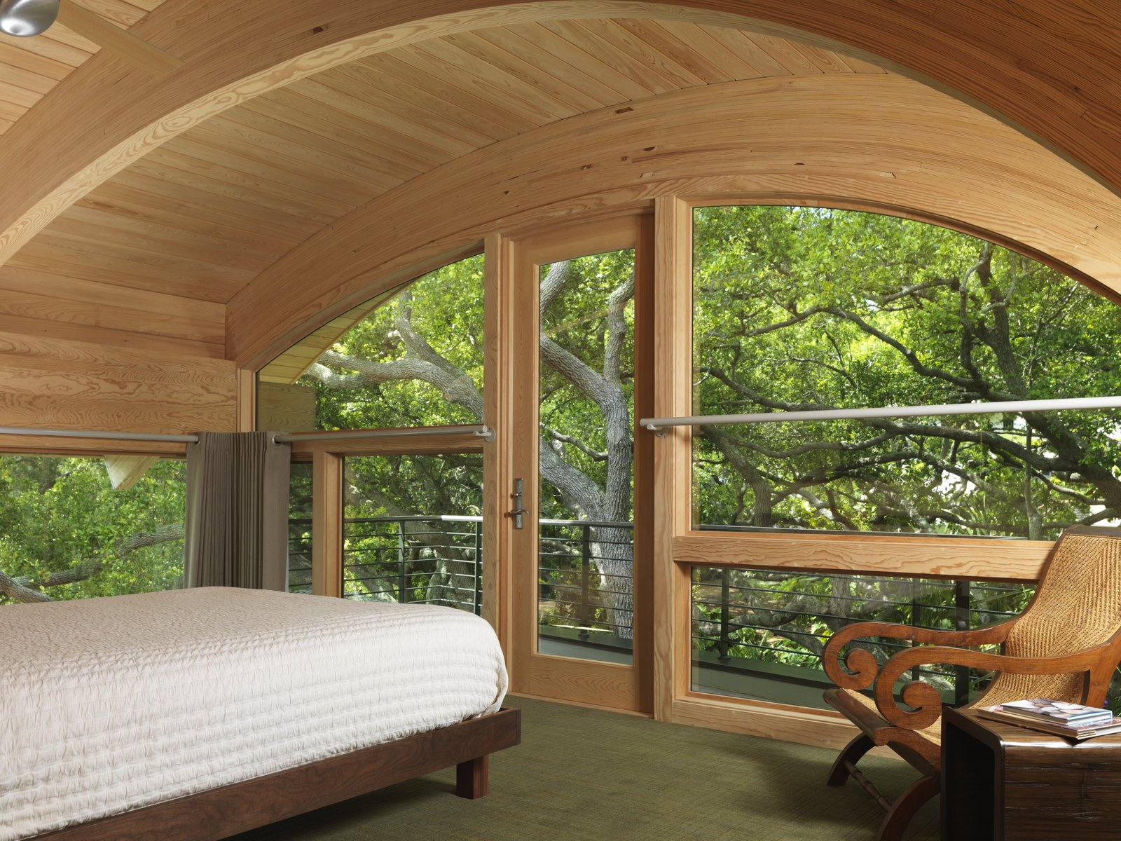 Casey Key House  In this playful treehouse-style bedroom, custom arched windows surround the room and meet the wooden ceiling. Elements of wood and modern architecture draw the sound of rustling leaves and midday breeze into this cozy treetop retreat.  Architect: Jerry Sparkman; Architecture Firm: Sweet Sparkman Architects; Location: Casey Key, FL   #marvin #windows #doors  #indoor #outdoor #transition #caseykeys #FL