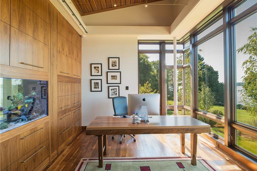 Photo courtesy of Holmes, King, Kallquist & Associates provided by Marvin Windows and Doors; project submitted to 2017 Marvin Architects Challenge Tagged: Office, Desk, Study, and Medium Hardwood Floor.  Modern Waterfront Residence by Marvin Windows and Doors