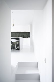 10 Minimalist and Monochromatic Homes in Belgium - Photo 1 of 10 - Niels & Annemie is a minimal residence located in Brussels, Belgium, designed by Benoît Deneufbourg and la fabrika studio.  The design brief was clear; Niels and Annemie wanted to keep the classical 'Hausmann grandeur' (high ceilings, large rooms, white walls, wooden floors) and combine this with modern lines and materials. The design approach was to keep it simple by using a black and white color scheme as the basis throughout the apartment. Their collection of Scandinavian and Italian furniture mixed with some original vintage pieces complements this refined interior, effortlessly blending old and new.